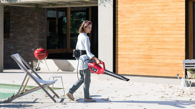 Model wearing Honda cordless belt and using a leaf blower in a garden location.