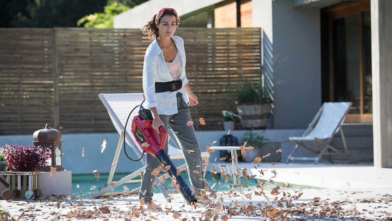 Model using Honda cordless leaf blower in garden location.